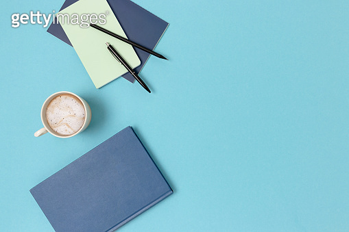 Top view of mug of coffee, pencil, book and copybooks on a blue pastel background.