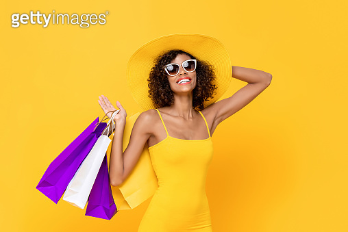 Summer portrait of smiling African American woman wearing sunglasses holding shopping bags