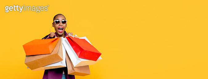 Beautiful fashionable African American woman holding colorful shopping bags