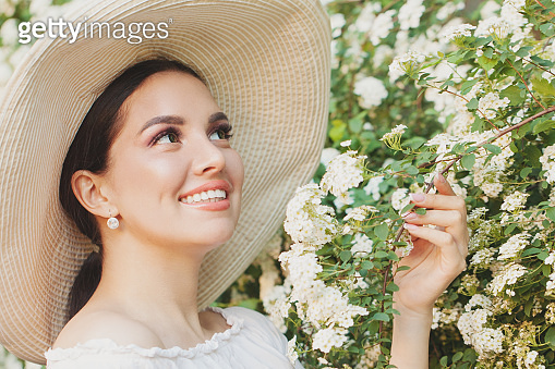 Elegant woman in hat with summer flowers outdoors