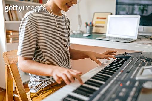 Teenage boy having online keyboard lesson