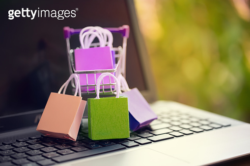 Paper shopping bags in a trolley or shopping cart on keyboard. Concept about online shopping that customers can buy everything from home or office and the messenger will deliver to the doorstep.