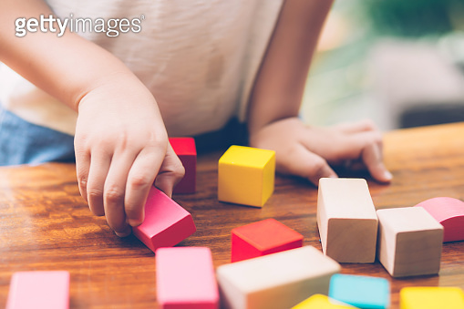 Closeup hand of boy playing wooden block toy on table for creative and development with enjoy, happy child learn skill for activity puzzle and creativity for game on desk at home, education concept.