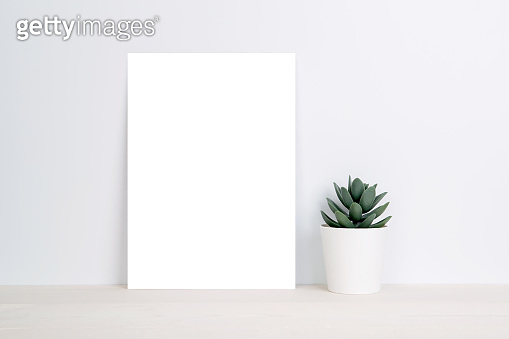 Blank paper sheet copy space with mockup and plants in potted on wooden table, poster and invitation with empty on desk, card decoration your design or branding, simplicity and minimal, nobody.