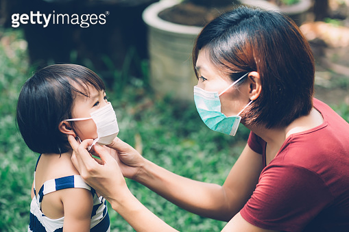 Mother take care daughter with face mask for protection disease flu or covid-19 outdoors, mom wearing on medical mask with child safety for protect outbreak of pandemic, medical concept.