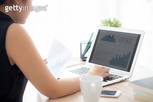 Beautiful young asian woman working and typing with laptop computer at office, businesswoman looking graph diagram analysis statistic data of finance, girl using notebook, profit growth, business concept.