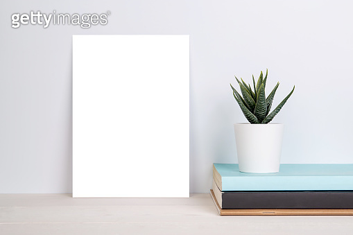 Blank mockup paper sheet copy space and plants in potted on book on wooden table, poster and invitation with empty on desk, card decoration your design or branding, simplicity and minimal, nobody.