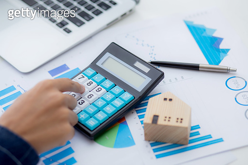 Hand of business man agent calculating loan of finance and investment for real estate, businessman and invest in property about home, construction or mortgage of home, male using calculator.