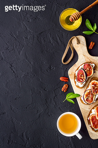 Toasted bread with figs, ricotta and honey on wooden cutting board