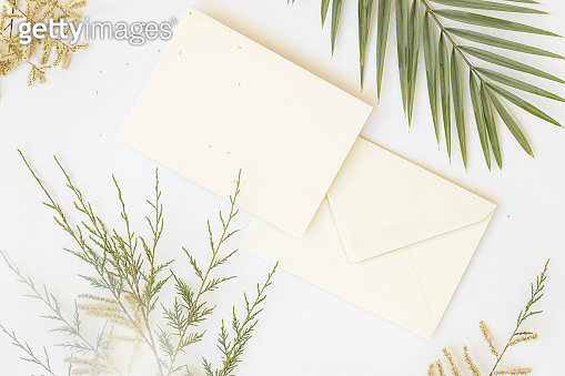 Mockup of white papers and envelope with Tropical palm leaf on gray background, and text space at center. Top view flatlay
