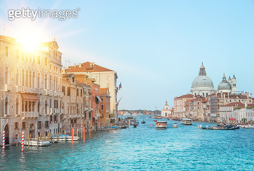 Sun flash and old cathedral of Santa Maria della Salute. The colorful venice view for historic architecture background.