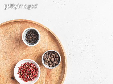 Kitchen minimalism concept. Various spices in small bowl on wood tray on light background. Top view. Copy space
