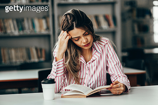 Tired woman studying at table in library