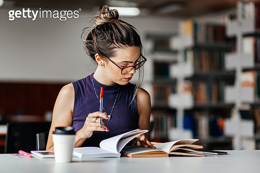 Young woman studying at table in library