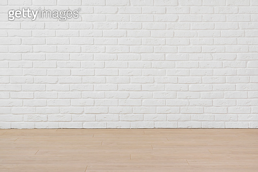 Empty room with white brick wall and laminated flooring board