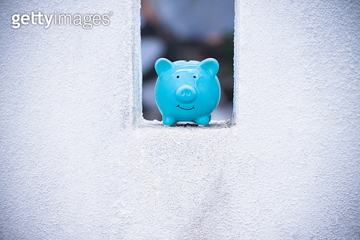 Blue piggy Bank standing at concrete white wall.