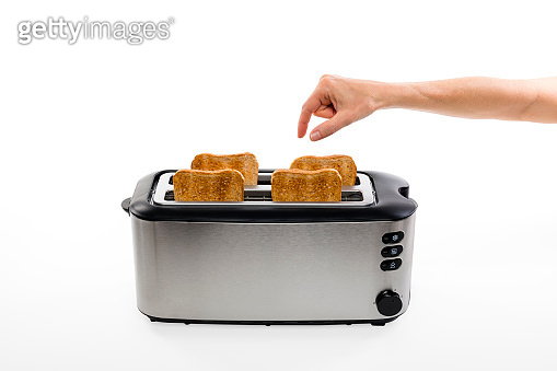 hand is picking fresh crispy toastbread out of a toaster