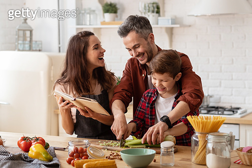 Happy family laughing loud and cooking on kitchen