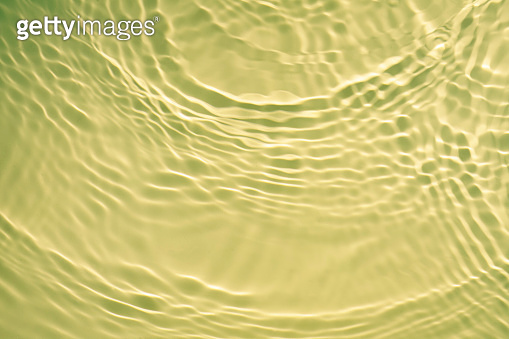 Yellow gold liquid cosmetic water gel with circular rippling wave effect