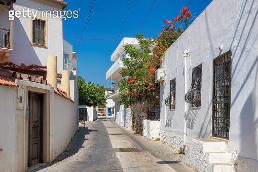 Old cozy street with flowers in white houses in Mediterranean trown