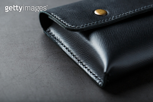 Black wallet made of genuine leather on a dark background. Handmade leather items