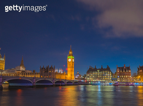 Big Ben and Houses of Parliament at Westminster bridge over Thames river at night in London, UK