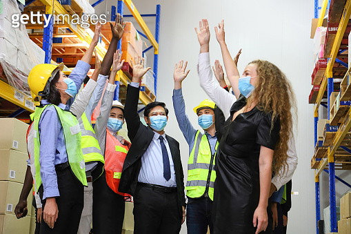Manager and the rest of the engineering team standing together in the factory wearing facial mask with assembling hand to fight against obstacle during new normal and social distancing