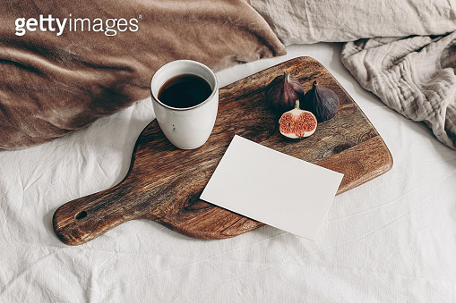 Autumn breakfast in bed composition. Blank greeting card mockup, cup of coffee and fig fruit on wooden cutting board. White linen background. Velvet cushions. Thanksgiving, fall concept. Top view.