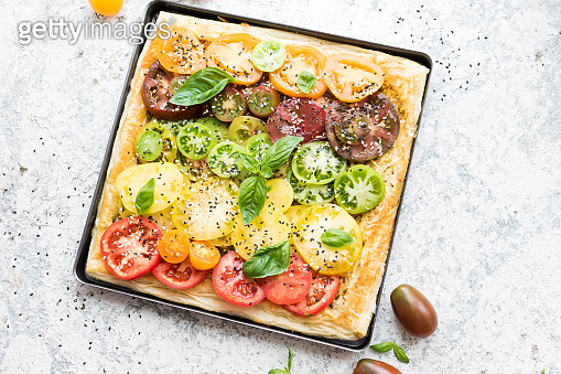 Vegetable puff pastry tart with colorful tomatoes