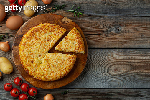 Spanish omelette with potatoes and onion, typical Spanish cuisine. Tortilla espanola. Rustic dark background. Top view with copy space