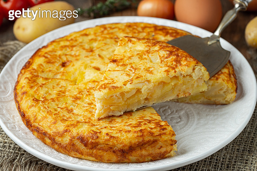 Spanish omelette with potatoes and onion, typical Spanish cuisine. Tortilla espanola. Rustic dark background