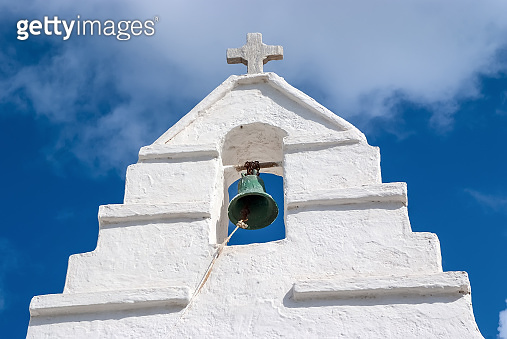 Bell tower with cross in Mykonos, Greece. Chapel building detail architecture. White church on cloudy blue sky. Religion and cult concept. Summer vacation and travel on mediterranean island