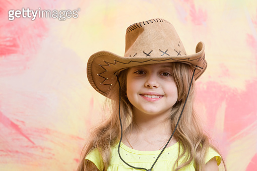 little girl in cowboy hat on colorful background, copy space