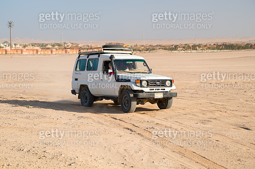 Off road car drive on desert landscape. Jeep for safari on sunny blue sky. Truck automobile travel in sand dune. Wanderlust and adventure. Challenge, speed and extreme concept