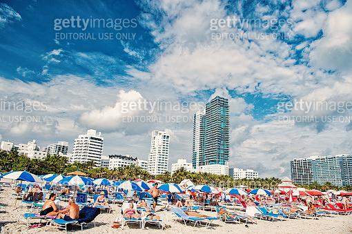 People sunbathing on deck chairs under blue umbrellas