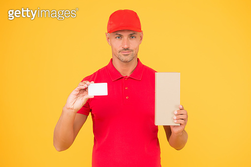 Got loyalty card. Courier hold discount card and box. Parcel delivery. Handsome man show blank card for business information. Online shopping. Shop and pay with credit card, copy space