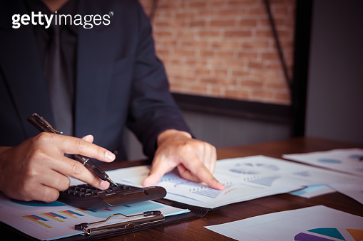 asian business man working with new startup project hand pointing graph discussion and analysis data charts and graphs and using a calculator to calculate  numbers.Business finances and accounting concept
