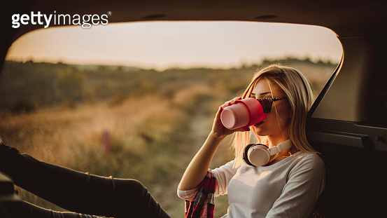 A blonde woman drinking her coffee in nature - Beautiful sunset in nature - A young beautiful blonde woman sits in the open trunk of her car and enjoys the sunset