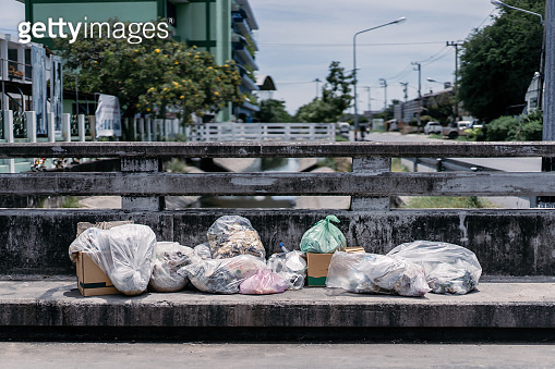 a pile of garbage are dropped on the footpath over the canal bridge in the midday time.
