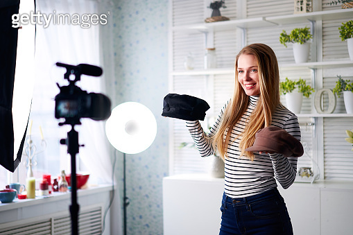 Fashion blogger woman in jeans and turtleneck showing fashionable caps on camera. Stylist influencer girl showing trendy hats filming vlog episode for her video channel. Opinion leader sets trends