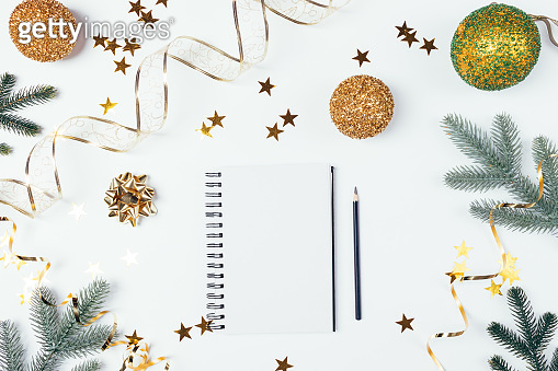 Christmas flat lay composition blank notebook among golden shiny decorations
