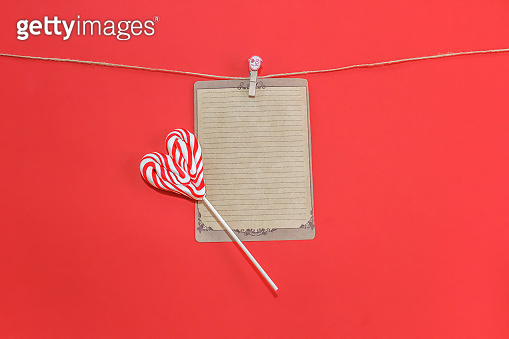 Valentines Card in retro style on pin and lollipops candy as heart on red. Valentine day concept.