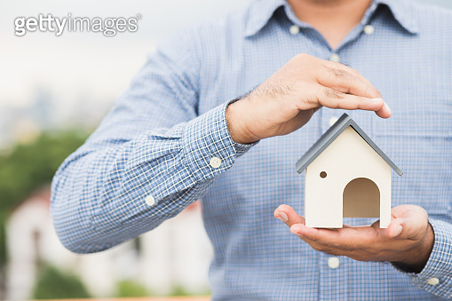 Hand holding mockup house. Real estate loan insurance buy and sell home concept.