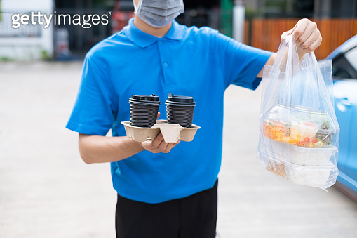 Food Delivery man wearing mask handing plastic bags shopping online from supermarket to client service customer front house, express grocery when coronavirus covid19 new normal lifestyle.