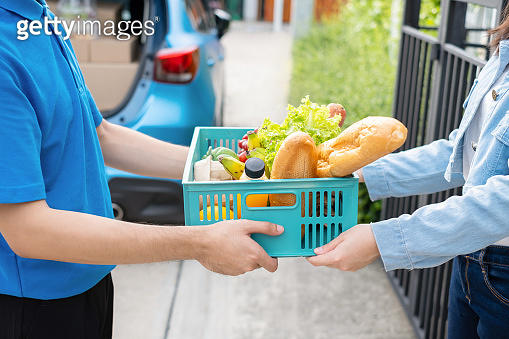 Food Deliver Asian man in blue uniform give fruit and vegetable to receiver customer front house, fast express grocery service when crisis coronavirus, covid19 new normal lifestyle concept.