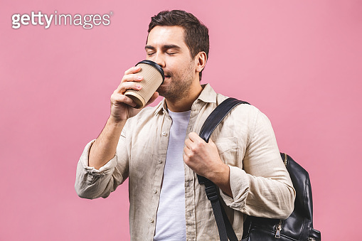 Young handsome man with backpack holding coffee cup isolated on pink background. Smiling student portrait. Studio shot of cheerful men going on travel.