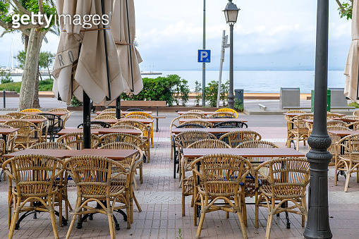 Empty tables on the terrace of a summer cafe on the Mediterranean promenade