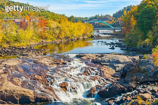 Idyllic stream and Rumford Falls surrounded by beautiful autumn foliage colors.