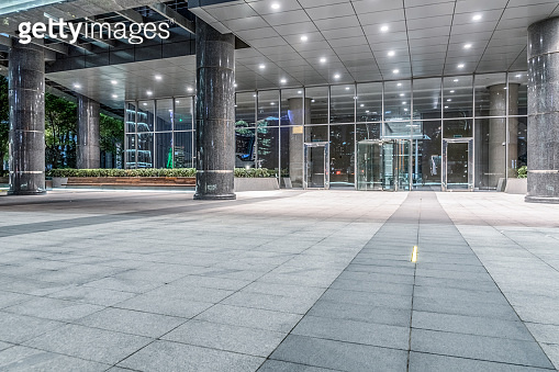 night view of empty brick floor front of modern building