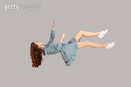 Floating in air. Relaxed girl in vintage ruffle dress levitating keeping eyes closed, sleeping while flying mid-air